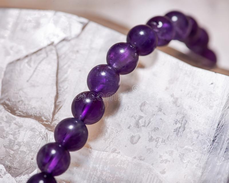Pulsera púrpura real de la gota de la amatista envuelta alrededor de punto del cuarzo del arco iris de Lemurian del Brasil en la  foto de archivo libre de regalías