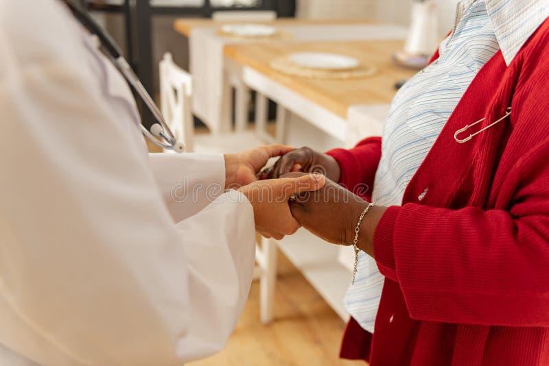 Pulsera que lleva de la mujer que sacude las manos de su cuidador que cuida fotos de archivo