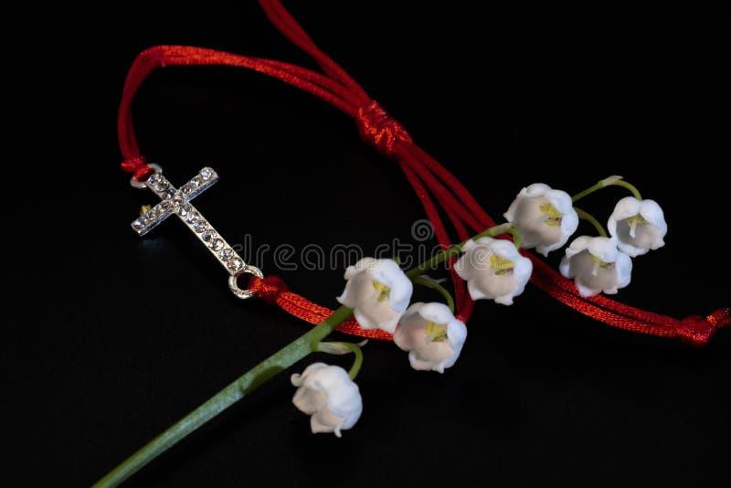 Pulsera roja del encanto del cordón y flor blanca del lirio de los valles fotografía de archivo libre de regalías