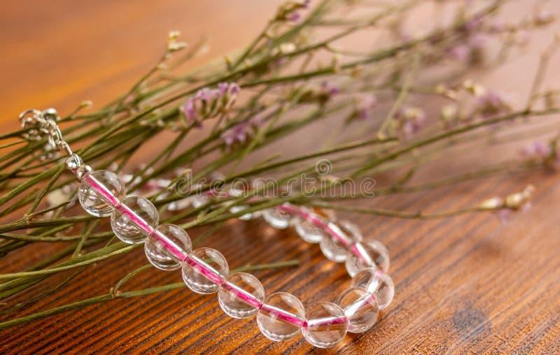 Pulsera y flores cristalinas del cuarzo en la tabla de madera imagenes de archivo