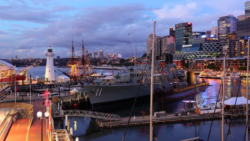 Pulserende stad bij haven met marineschip door schemer royalty-vrije stock fotografie