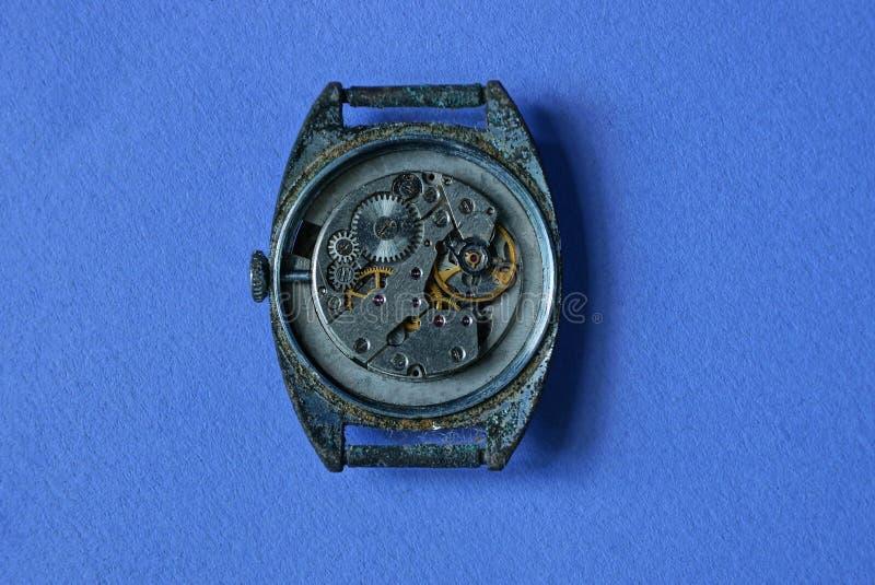 pulso de disparo sujo velho com uma mentira aberta do mecanismo em uma tabela azul fotografia de stock royalty free