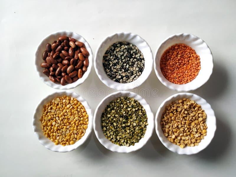 Pulsos crudos, granos y semillas en los cuencos blancos sobre fondo del ston Foco selectivo imagenes de archivo