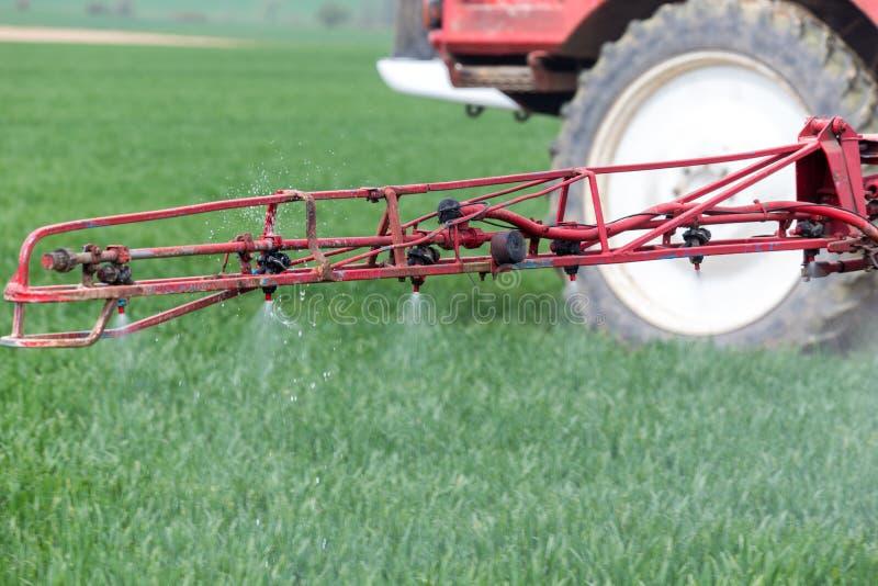 Pulvérisation des herbicides sur le grand champ vert images libres de droits