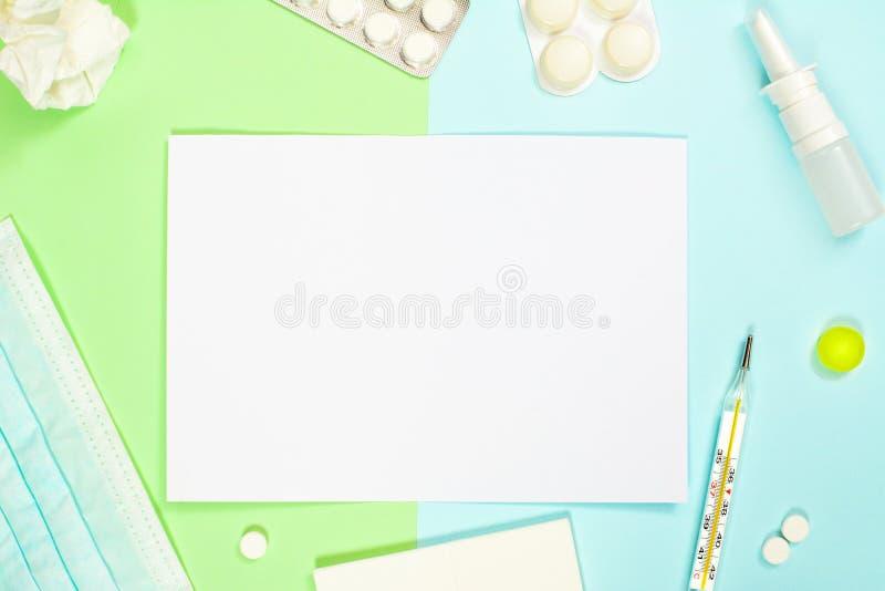 Pulvérisation nasale, médecines, thermomètre, mouchoirs, masque médical sur le fond vert-bleu Traitement de froid et de grippe images libres de droits