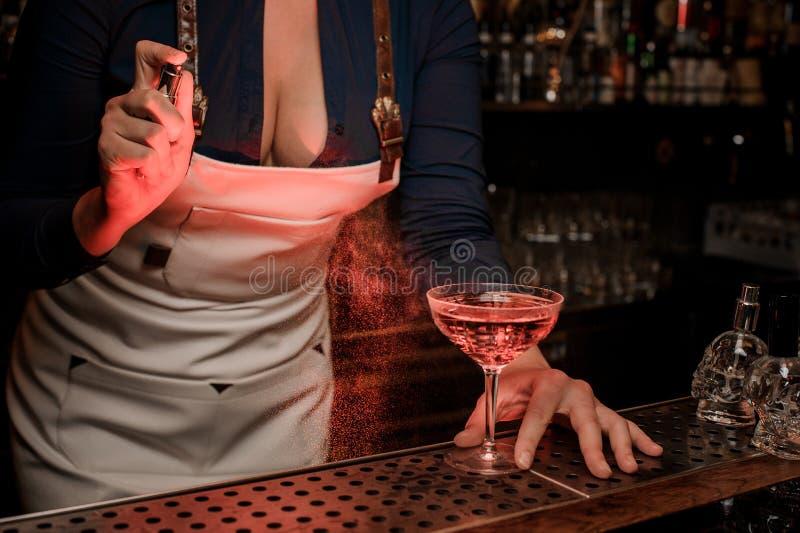 Pulvérisation sexy de barmaid amère sur le verre de cocktail élégant photographie stock libre de droits