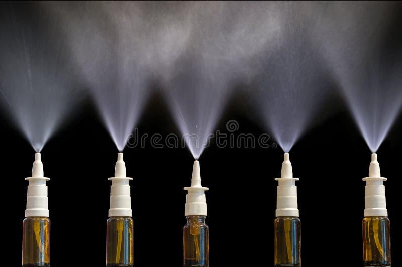 Pulvérisations nasales de pulvérisation devant le fond noir photo stock