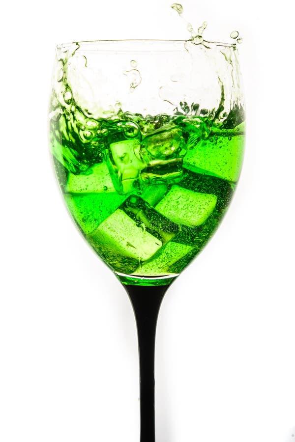 Pulvérisez des glaçons en baisse dans un verre de vin photo stock