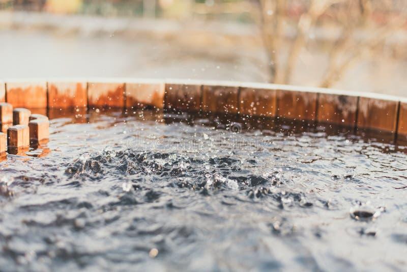 Pulvérisez l'eau propre dans un puits rempli Puits en bois avec de l'eau photo libre de droits