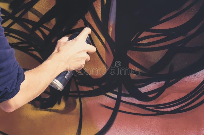 Pulvérisez la peinture d'aérosol pour le graffiti dans les jeunes de main de garçons images stock