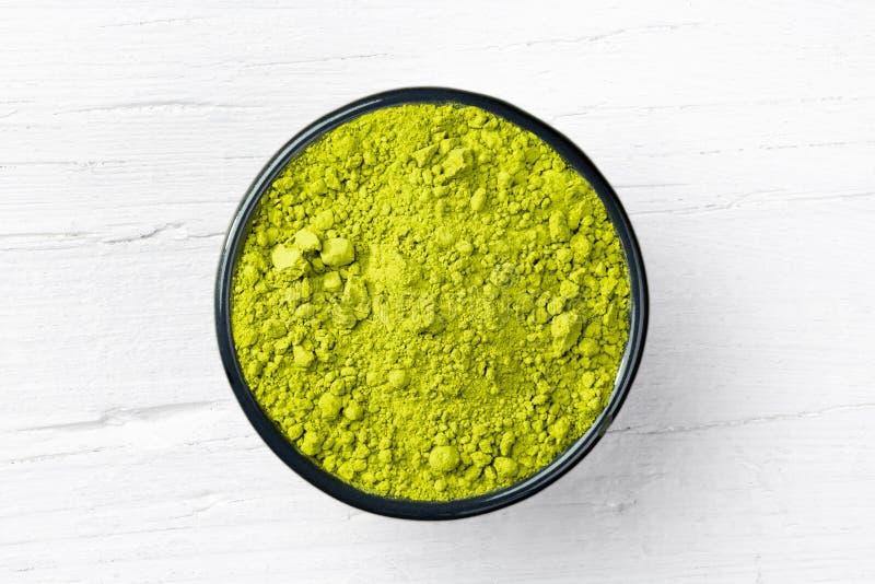 Pulver grünen Tees Matcha auf weißem hölzernem Hintergrund lizenzfreie stockfotos