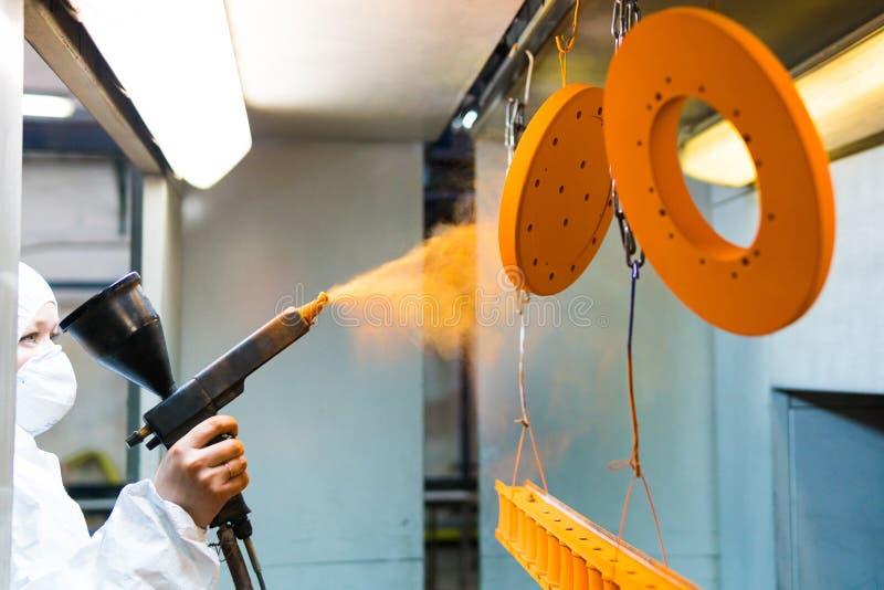 Pulverbeschichtung von Metallteilen Eine Frau in einem Schutzanzug sprüht Pulverfarbe von einem Gewehr auf Metallprodukten lizenzfreie stockfotografie