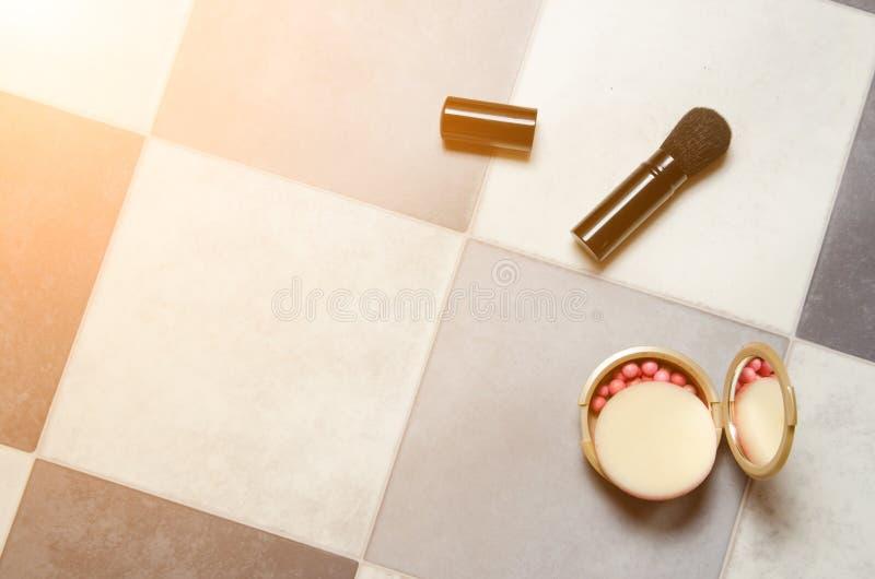 Pulverisieren Sie Kasten mit Spiegel und Make-upbürste auf kariertem Schwarzweiss-Hintergrund stockfotografie