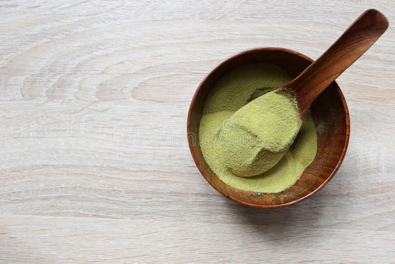 Pulverisieren Sie matcha grünen Tee in einer Schüssel auf hölzernem Hintergrund lizenzfreies stockbild