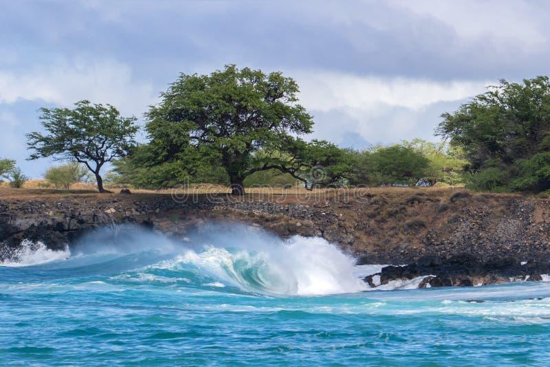 Pulverizador de mar de arrasto de ondulação da onda que quebra perto da costa na tira custada havaiana da terra no fundo com roch imagens de stock