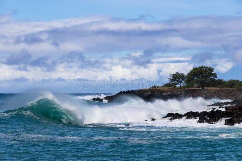 Pulverizador de mar de arrasto de ondulação da onda que quebra perto da costa na tira custada havaiana da terra no fundo com roch fotos de stock royalty free