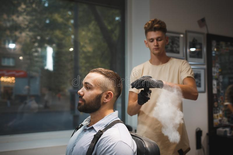 Pulverizador de pulverização da fixação do cabelo do barbeiro em um cliente em um fundo borrado Conceito profissional do cabeleir foto de stock royalty free