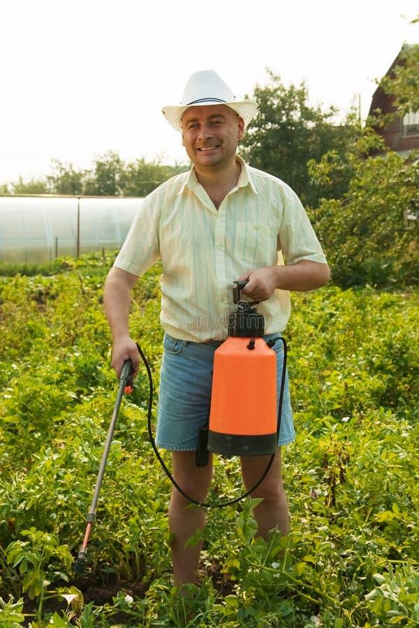 Pulverizador e funcionamento do jardim da terra arrendada do homem fotos de stock royalty free