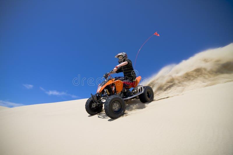 Pulverizador grande da areia do cavaleiro do quadbike de ATV na duna imagens de stock