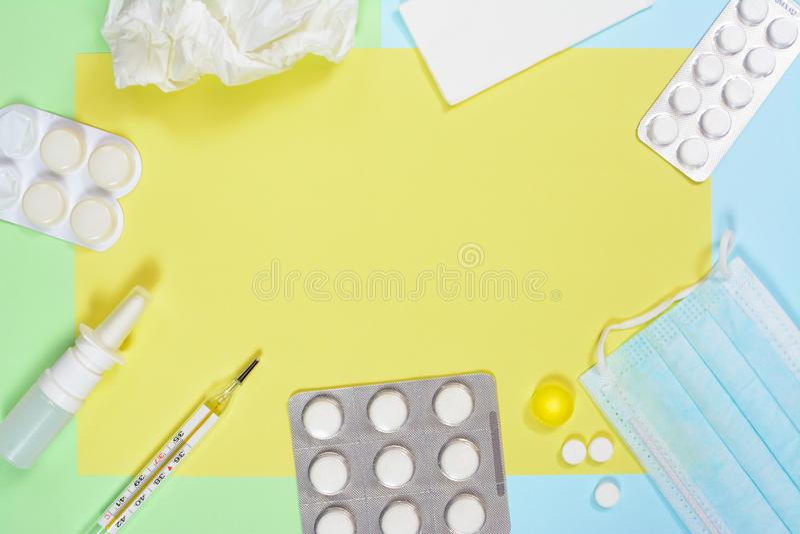 Pulverizador nasal, lenços, termômetro, medicinas, máscara médica no fundo azul verde com bolha grande Frio e gripe imagens de stock