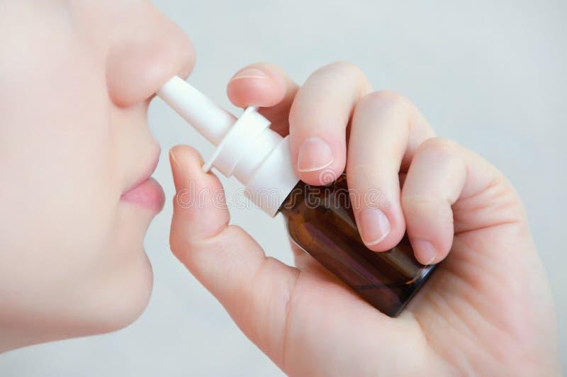 Pulverizador nasal Mulher nova bonita Cara com gotas nasais Close-up do pulverizador nasal médico de pulverização fêmea em seu na imagem de stock