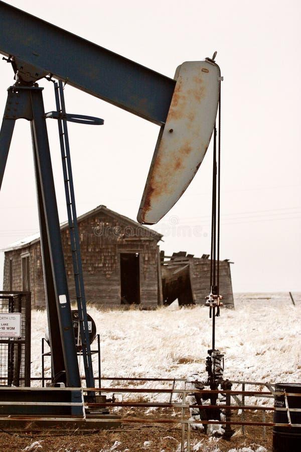 Pump jack near abandoned homestead stock photography