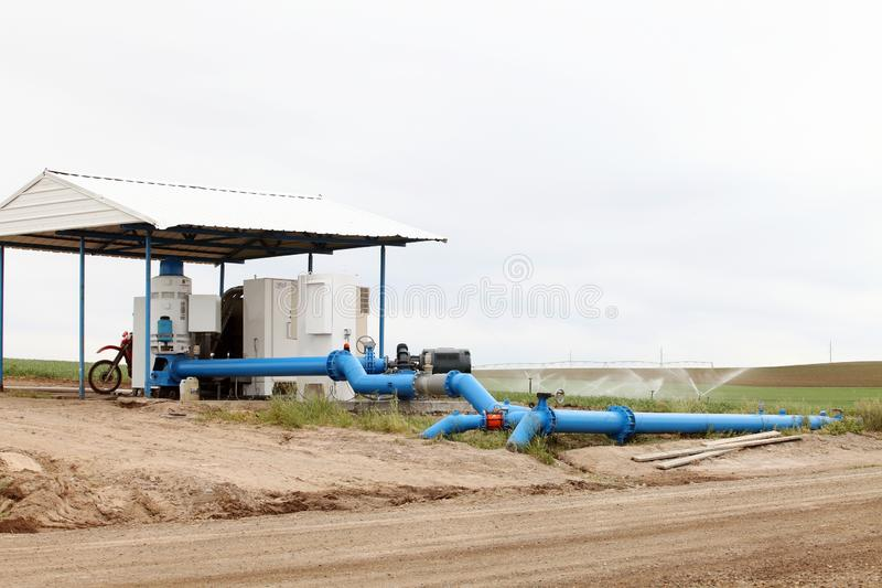 A pump and distribution center for an agricultural sprinkler system. A pump and pipes, make up the distribution center for an agricultural sprinkler system royalty free stock photo
