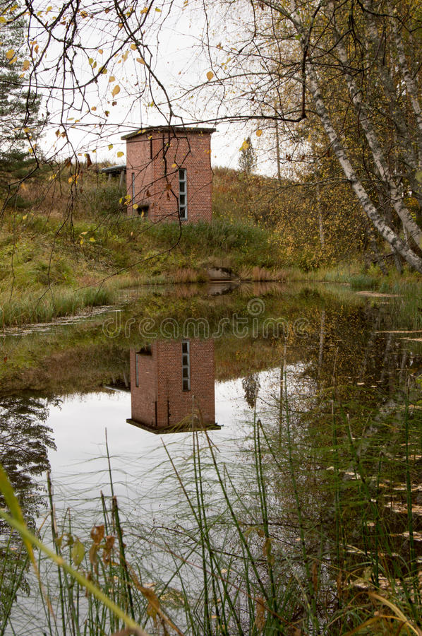 Pump station. Water pumping station mirrored from ditch. Fallen leafs on water royalty free stock photos