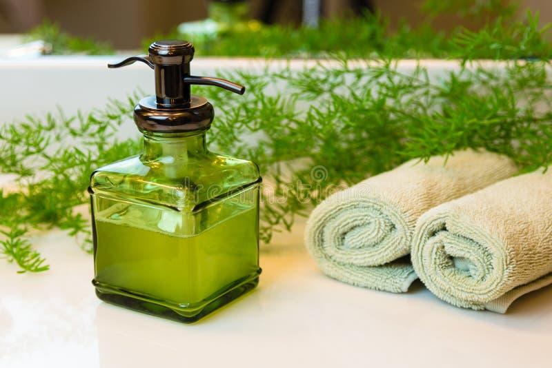 Pumpa flaskan med vätsketvål, handdukar och gräsplaner på badrumcoun arkivbilder