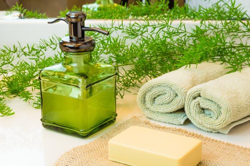 Pumpa flaskan med vätsketvål, stångtvål, handdukar och gräsplaner på slagträet arkivfoto