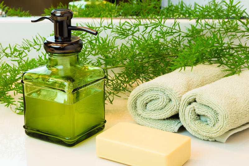 Pumpa flaskan med vätsketvål, stångtvål, handdukar och gräsplaner på slagträet royaltyfri bild