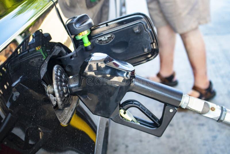 Pumpa gas - closeup av dysan för gaspump som sätts in in i till bilgasbehållare med ben av kunden i kortslutningar i bakgrund royaltyfri bild