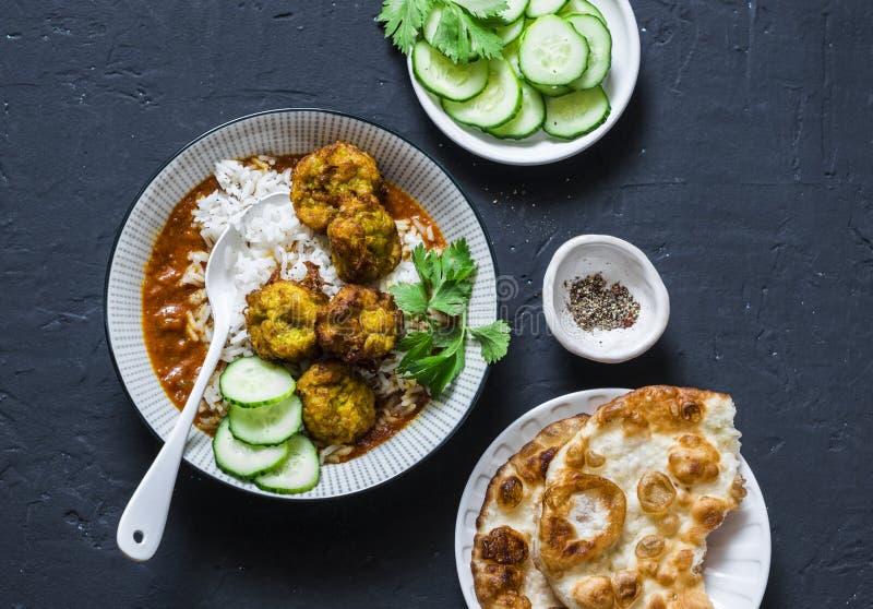 Pumpa- och zucchinistruvaköttbullar med ris- och currysås Sund vegetarisk mat på mörk bakgrund royaltyfria bilder