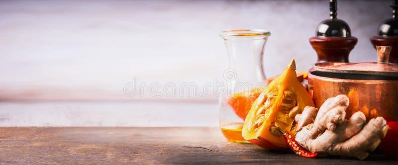 Pumpa på kökskrivbordtabellen med matlagningkrukan, olja och ingefäran, främre sikt Matbakgrund för höstmatlagninginspiration arkivbilder