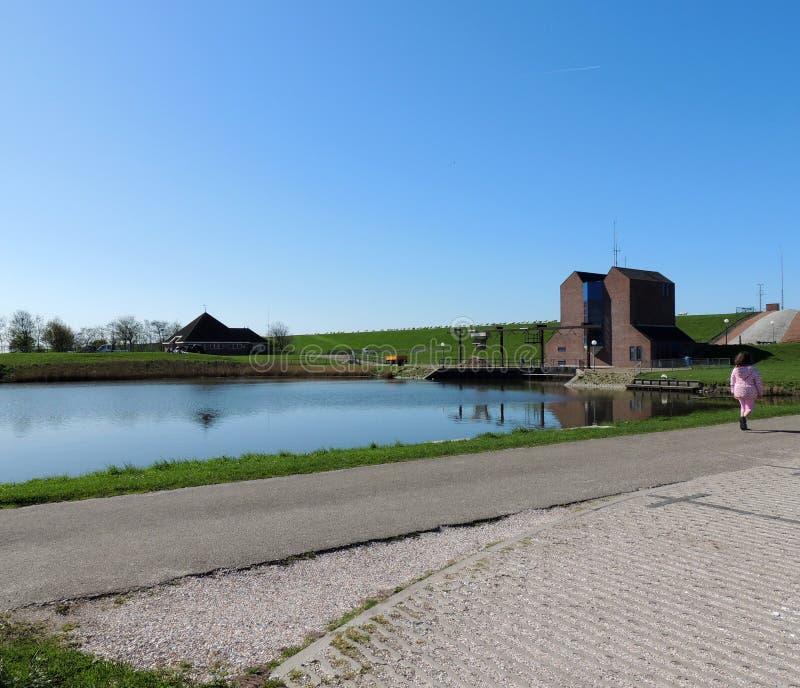 Pumpa station Nordpolderzijl Noordpolderzijl i landskapet av Groningen, Nederländerna Fördämning på Nordsjö arkivbild