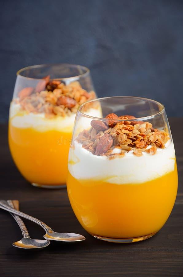 Pumpaefterrätt med yoghurt och hemlagad granola på den mörka trätabellen royaltyfria bilder