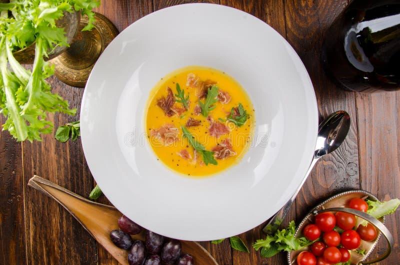 Pumpakrämsoppa med bacon och arugula i en vit platta på en mörk träbakgrund bland grönsaker royaltyfria foton