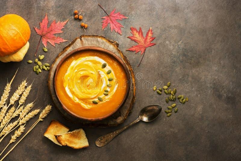 Pumpakrämsoppa med gräddfil och frö på en mörk grungebakgrund Värmehöst- och vintersoppa ?ver huvudet sikt, kopia royaltyfria bilder