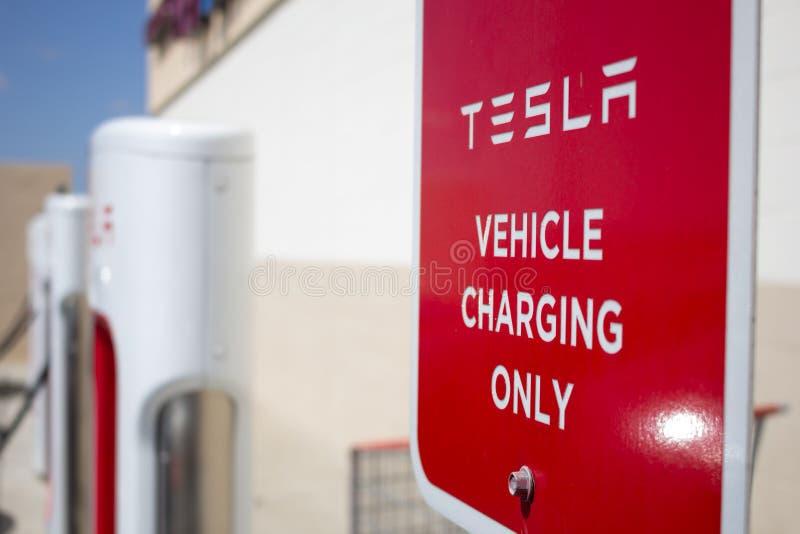 Pumpar för Tesla uppladdningsstation och designerat tecken royaltyfria foton