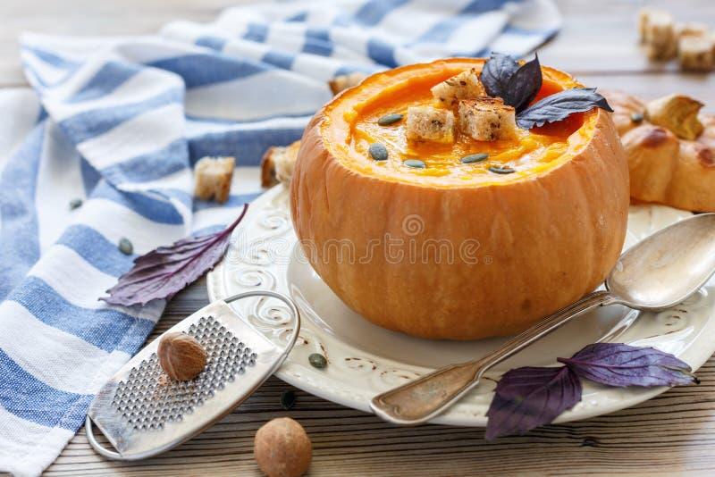 Pumpasoppa med kryddor och krutonger i pumpan royaltyfri fotografi