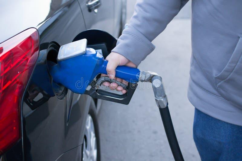 Pumpendes Gas an der Gaspumpe Nahaufnahme des pumpenden Benzinbrennstoffs des Mannes herein lizenzfreie stockbilder