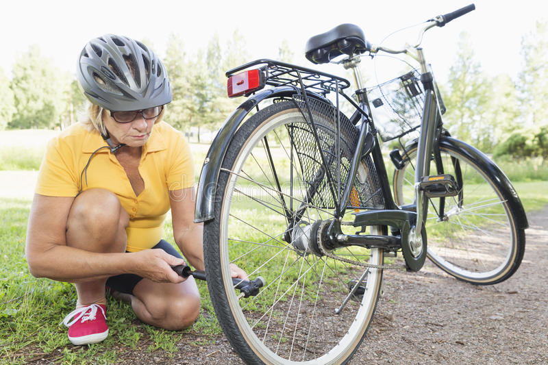Pumping air into bicycle tire. Senior woman pumping air into punctured step through bicycle tire at a park, wearing helmet royalty free stock photos