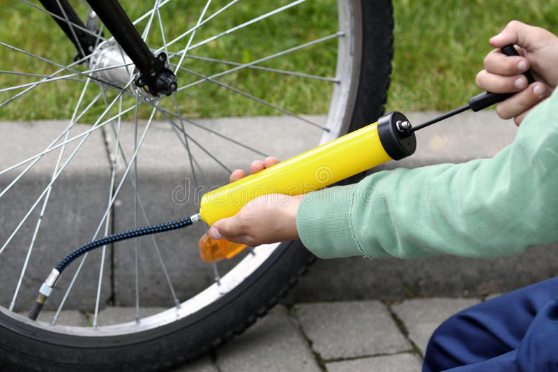 Pumping bicycle tire. Boy pumping his bicycle tyre, close-up on hands royalty free stock photo
