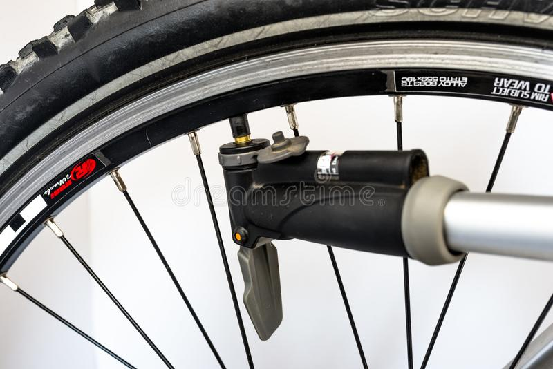 Pumping the bicycle wheel using a hand pump with air pressure indicator in units of bar / psi. stock image