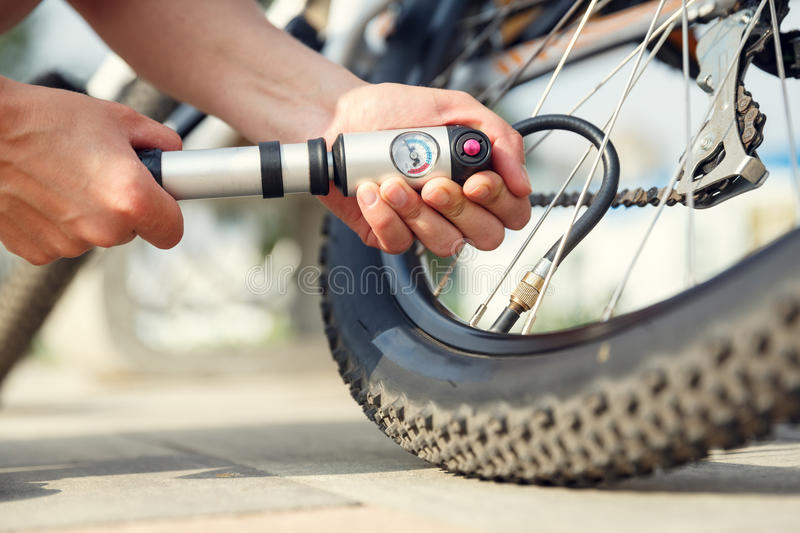 Pumping a bike tire. Woman`s hands pumping up a bike tire using small hand pump stock image