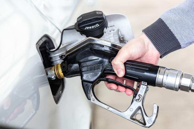 Closeup of mans hand pumping gasoline fuel in car at gas station. stock images