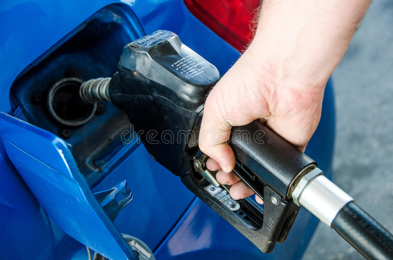 Pumping gas at gas pump. Closeup of a mans hand pumping gasoline fuel in car at gas station royalty free stock photo