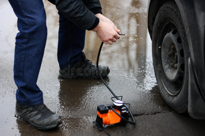 Pumping up the tyres of the vehicle. stock images