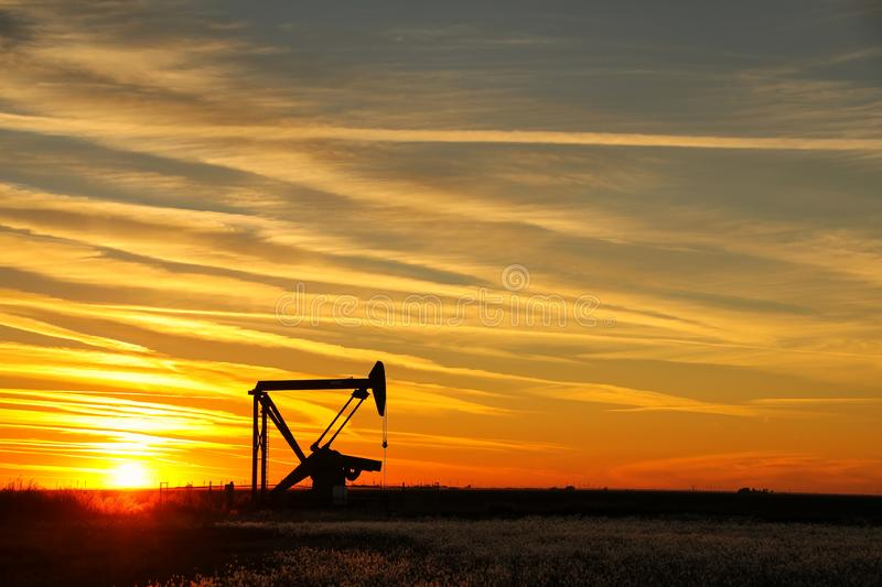 Pumpjack in the oil field at sunset royalty free stock photography