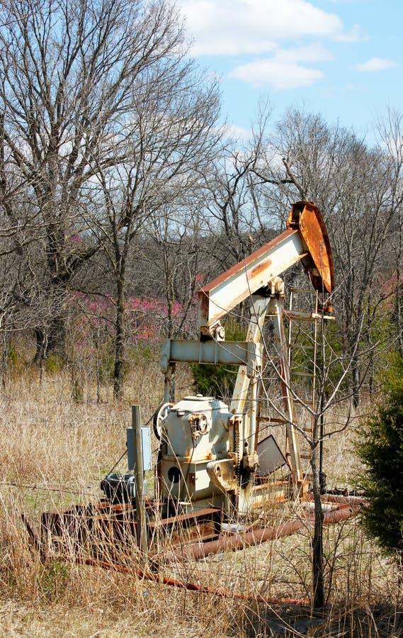 Pumpjack oxidado velho do poço de gás do óleo atrás da cerca do arame farpado fotografia de stock
